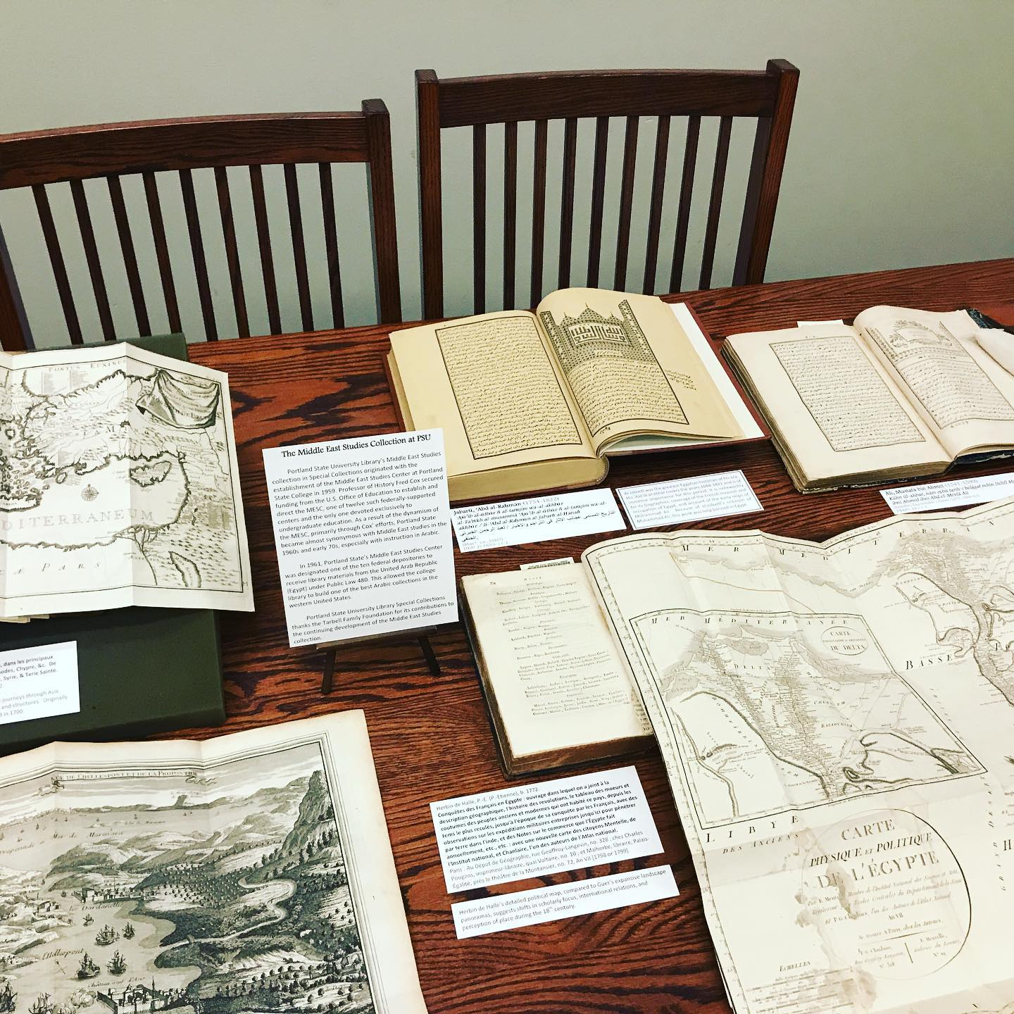 A collection of old books and maps on display on a wooden table.