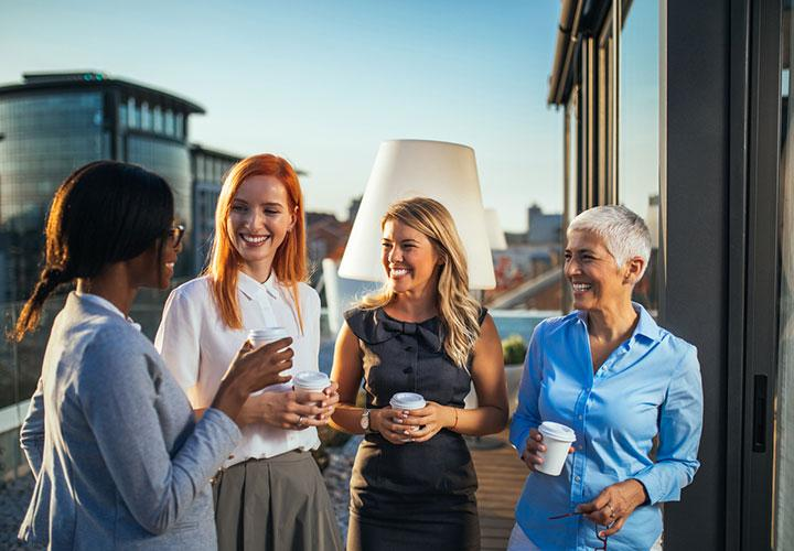 Smiling group of women drinking coffee and talking